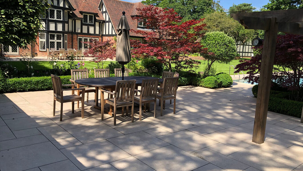 Large lawn with paved patio and seating area